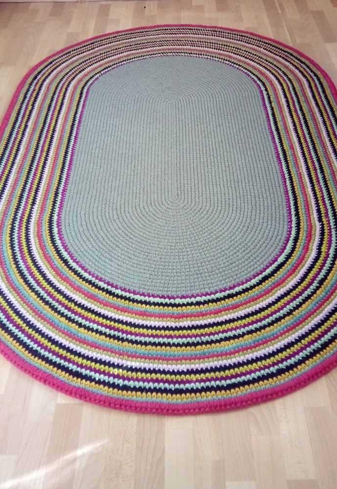 O rosa choque faz um lindo contraste com o preto e os tons mais claros desse tapete de crochê oval