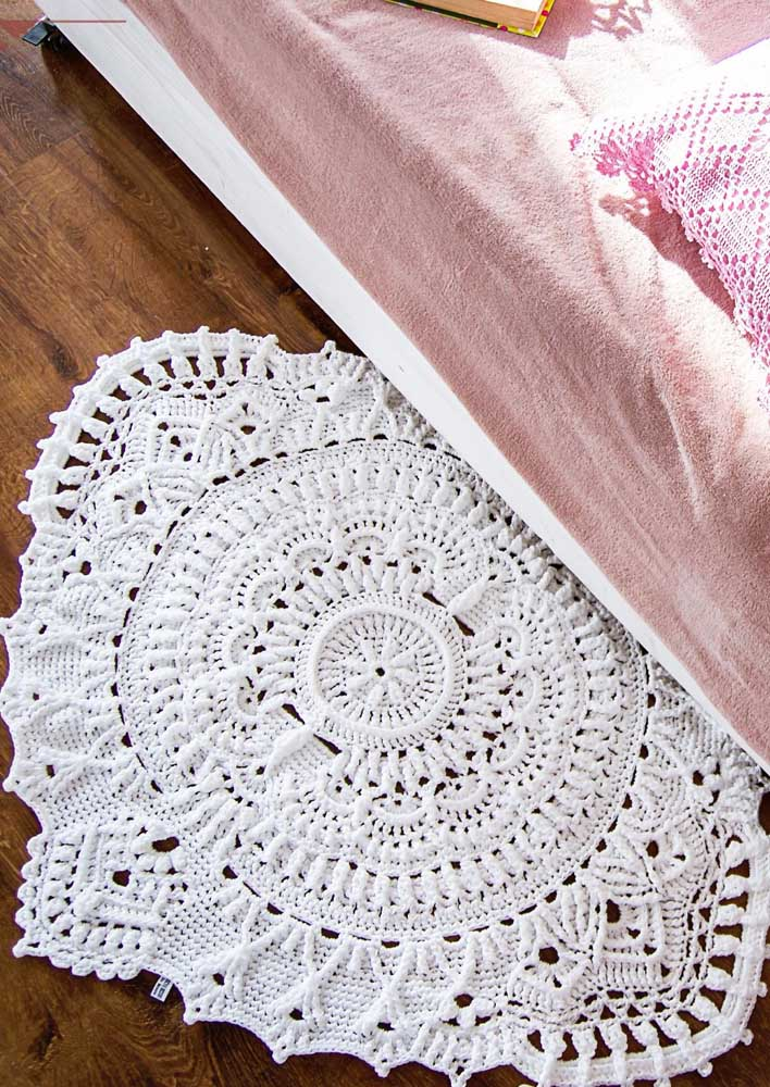 Desenho clássico e rebuscado para esse modelo branco de tapete de crochê oval