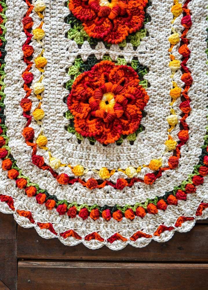 Tapete de crochê para banheiro de fundo cru e detalhes coloridos; o acabamento em flor é o grande diferencial desse tapete