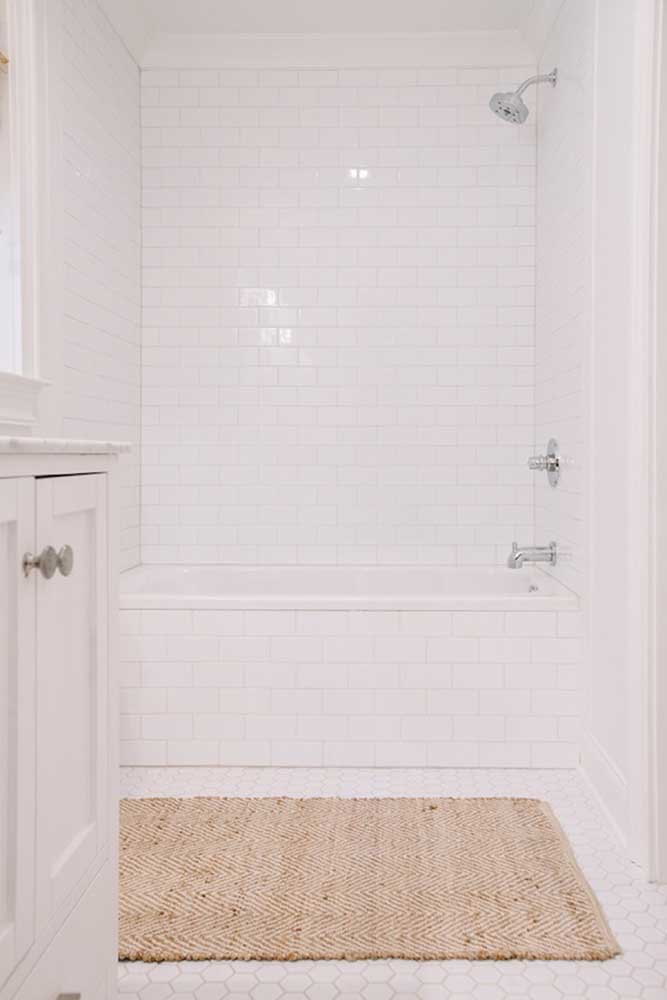 O banheiro branco e clean conta com um tapete de crochê em tom cru, mas que consegue se destacar muito bem diante da cor neutra