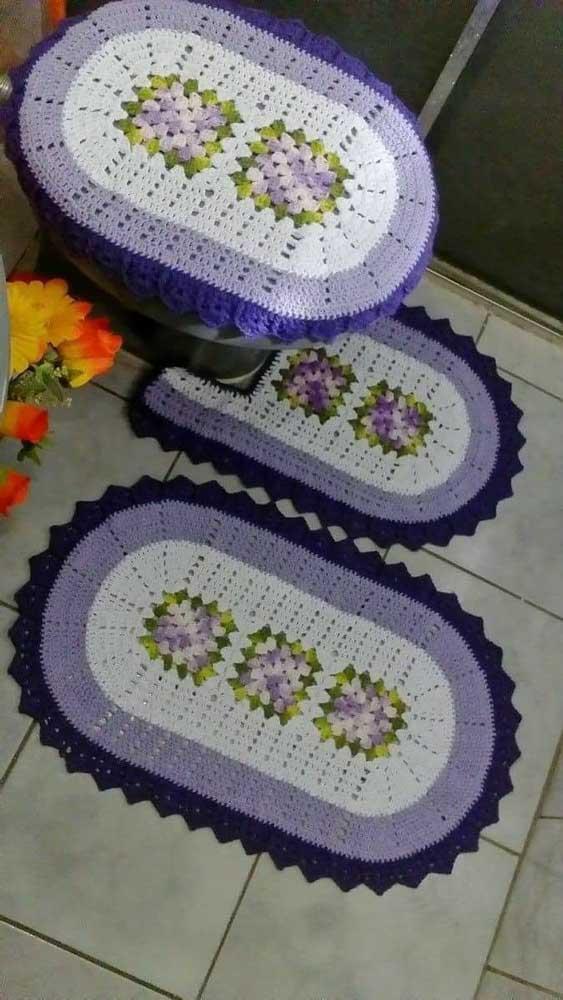 Jogo de banheiro em crochê branco e lilás; as flores completam a p+roposta delicada do kit