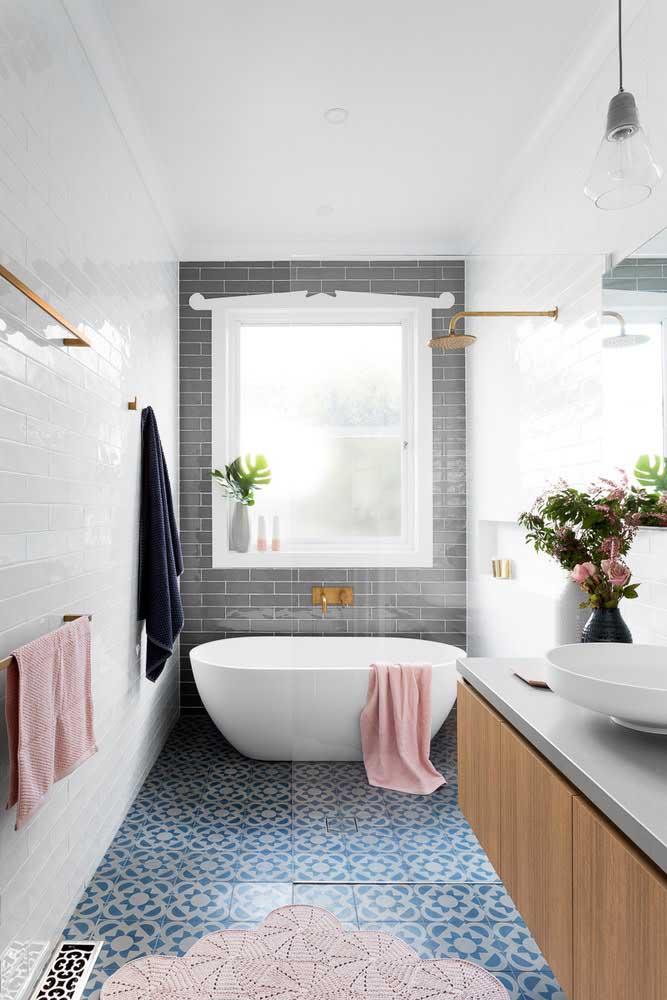 O rosa do tapete de crochê e das toalhas traz um aspecto romântico e delicado ao banheiro moderno