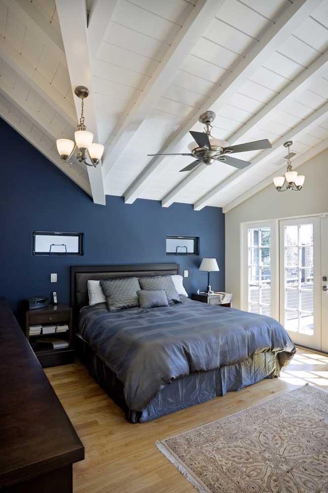 Olha o charme desse quarto com o piso de madeira, teto de madeira na cor branca e parede azul petróleo.