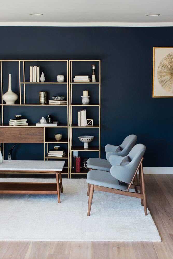 Os móveis de madeira com estofados na cor azul petróleo ficaram perfeitos nessa decoração de sala de estar.