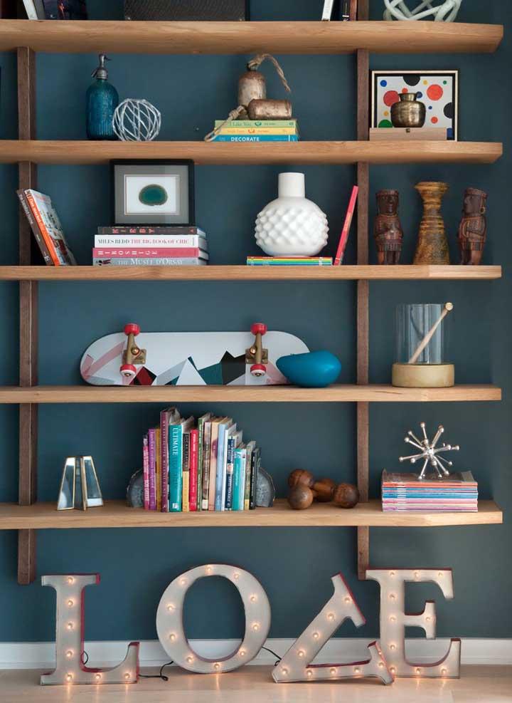 Na parede azul petróleo, coloque algumas prateleiras feitas de madeira para organizar os objetos de decoração.