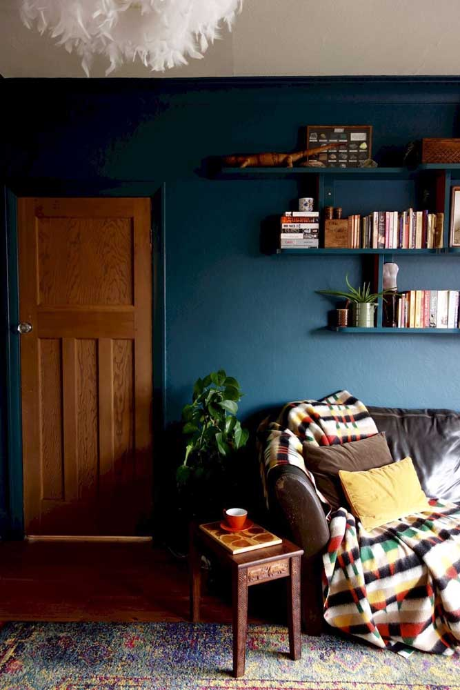 Perceba como a madeira faz uma combinação perfeita com a cor azul petróleo inserida na parede.