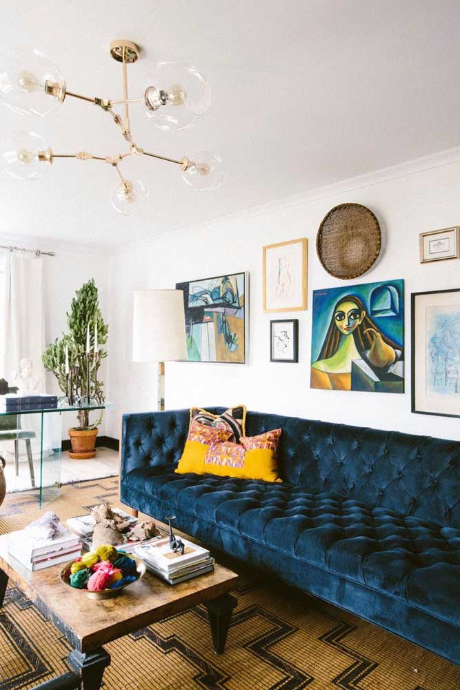 Que tal decorar a sala com um sofá na cor azul petróleo e um tapete na cor marrom?