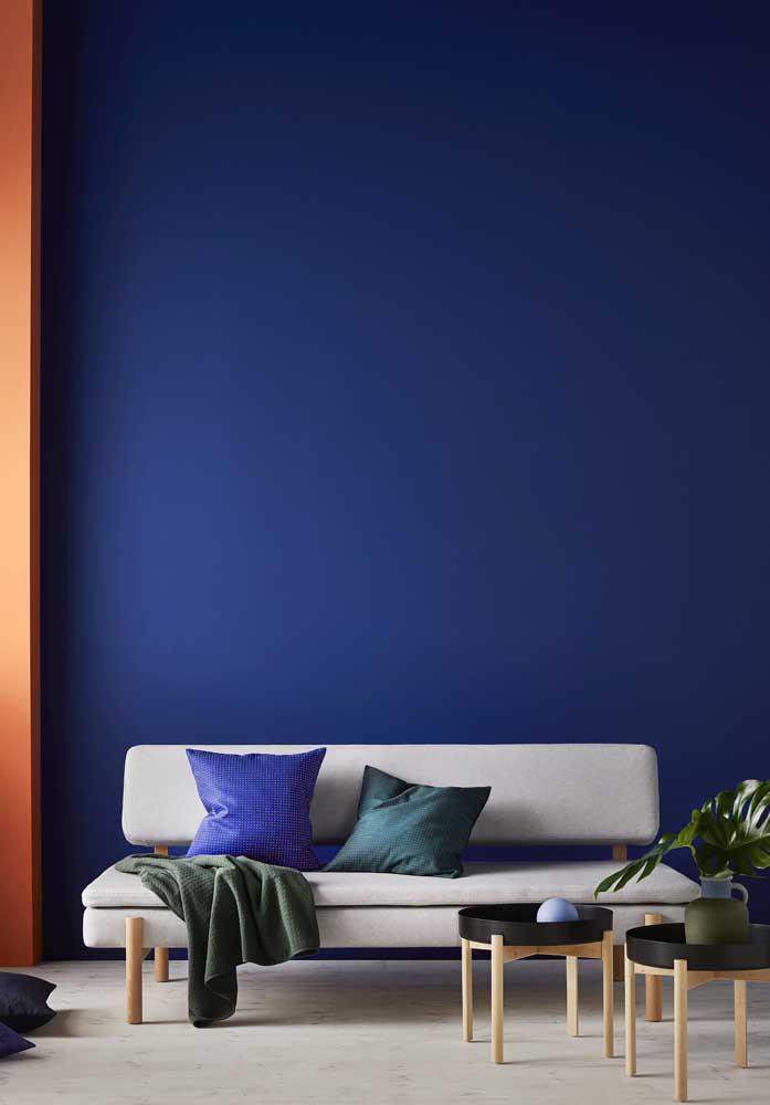 Incrível essa sala de estar com parede azul royal, a cor, inclusive, ajuda a destacar o pé direito alto; repare que foram usados poucos móveis e objetos decorativos justamente para não tirar o foco do azul royal