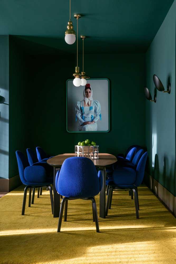 Lembra da combinação de cores análogas? Ela aparece aqui nessa sala de jantar entre o azul royal das cadeiras e o verde esmeralda das paredes