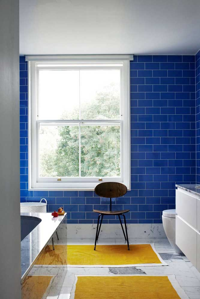 Esse banheiro optou pela combinação de cores complementares: azul royal na parede e amarelo nos tapetes