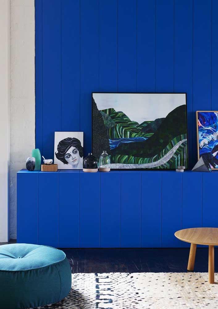 O buffet e o revestimento de madeira na parede seguem no tom azul royal; o branco ajuda a iluminar o ambiente