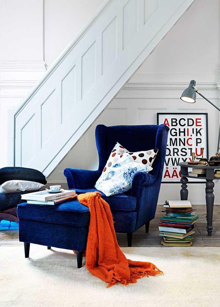 Uma combinação discreta de cores complementares: azul royal na poltrona e manta laranja