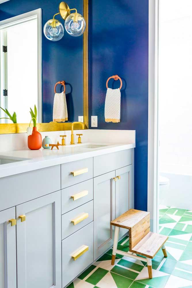 Topa um banheiro cheio de estilo como esse? Piso branco e verde, parede azul royal e detalhes dourados