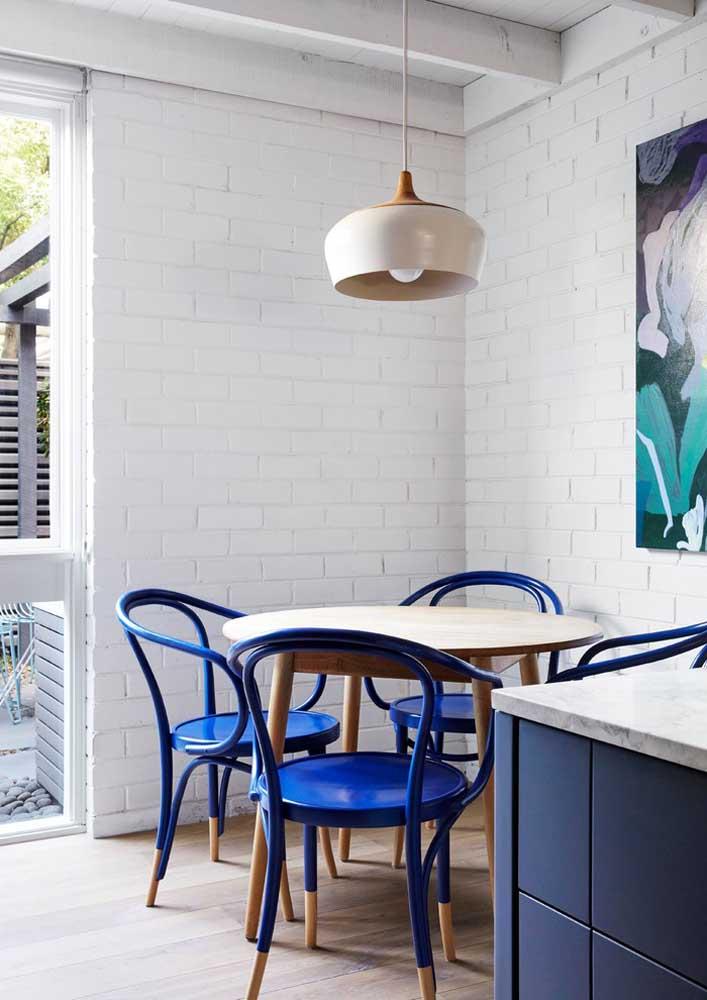 A sala de jantar branca apostou em cadeiras azul royal
