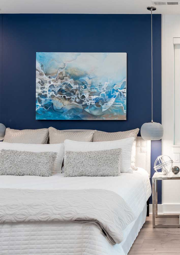 Nesse quarto de casal, a opção foi por pintar apenas uma das paredes em azul royal