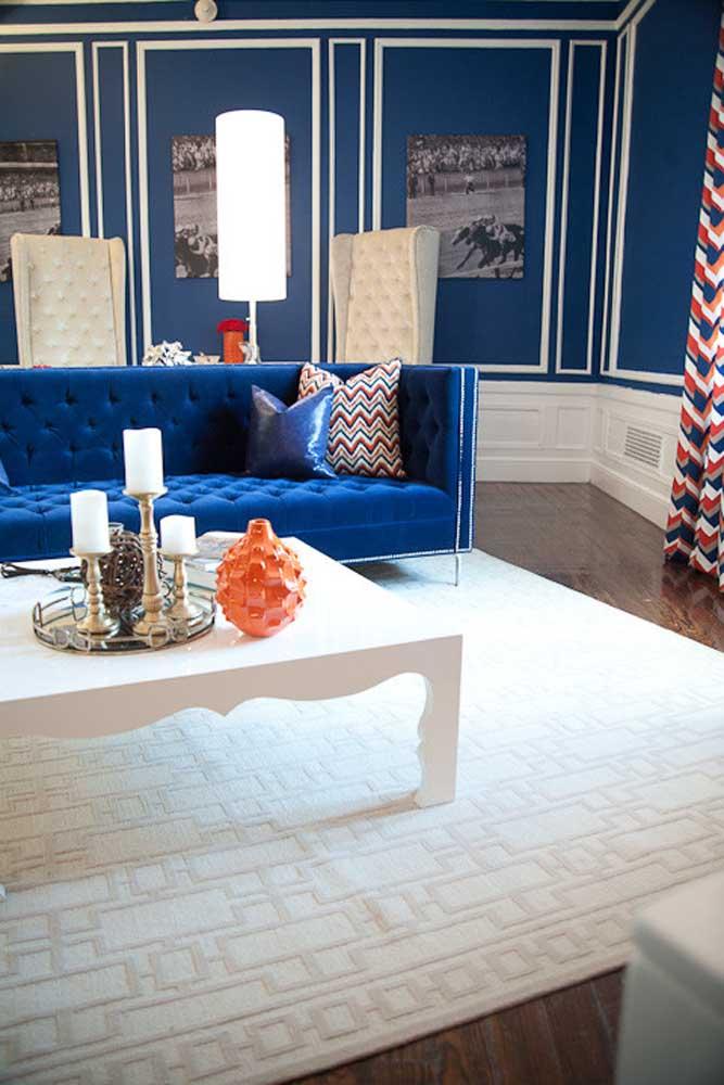 A parede com boisseries ficou mais destacada com a cor azul royal; o sofá a frente completa a proposta