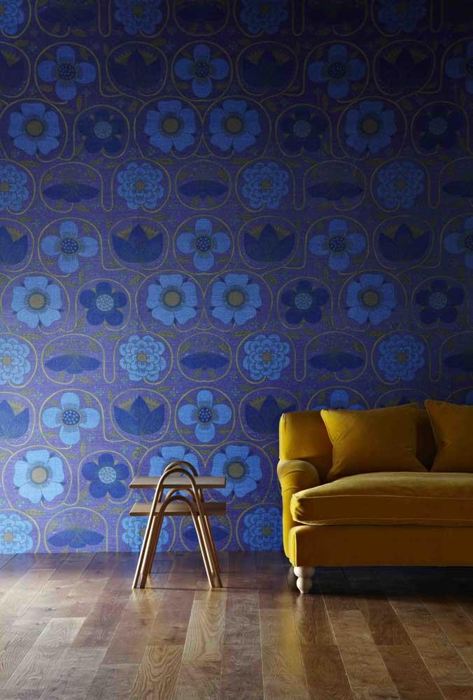 Aqui, o azul royal dá cor para as flores e folhas do papel de parede; para contrastar, a cor complementar do sofá
