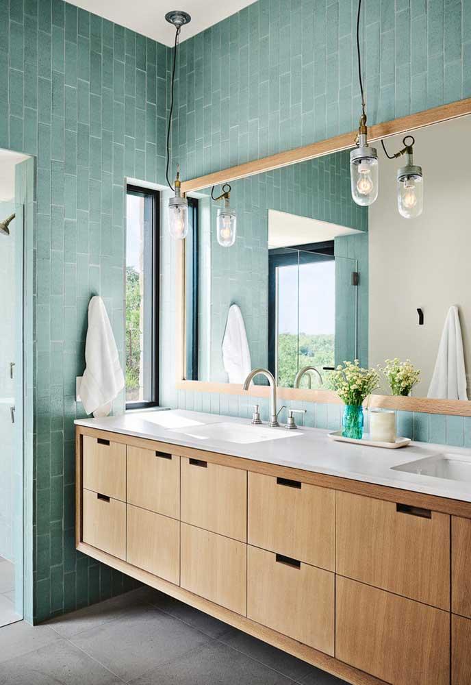 Que tal decorar o banheiro com móveis de madeira e a parede na cor azul turquesa?