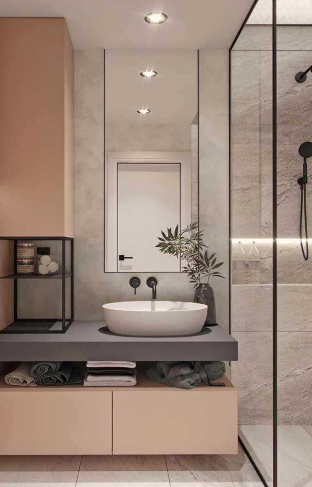 Banheiro pequeno com armários planejados; repare no truque do espelho refletindo a iluminação do local