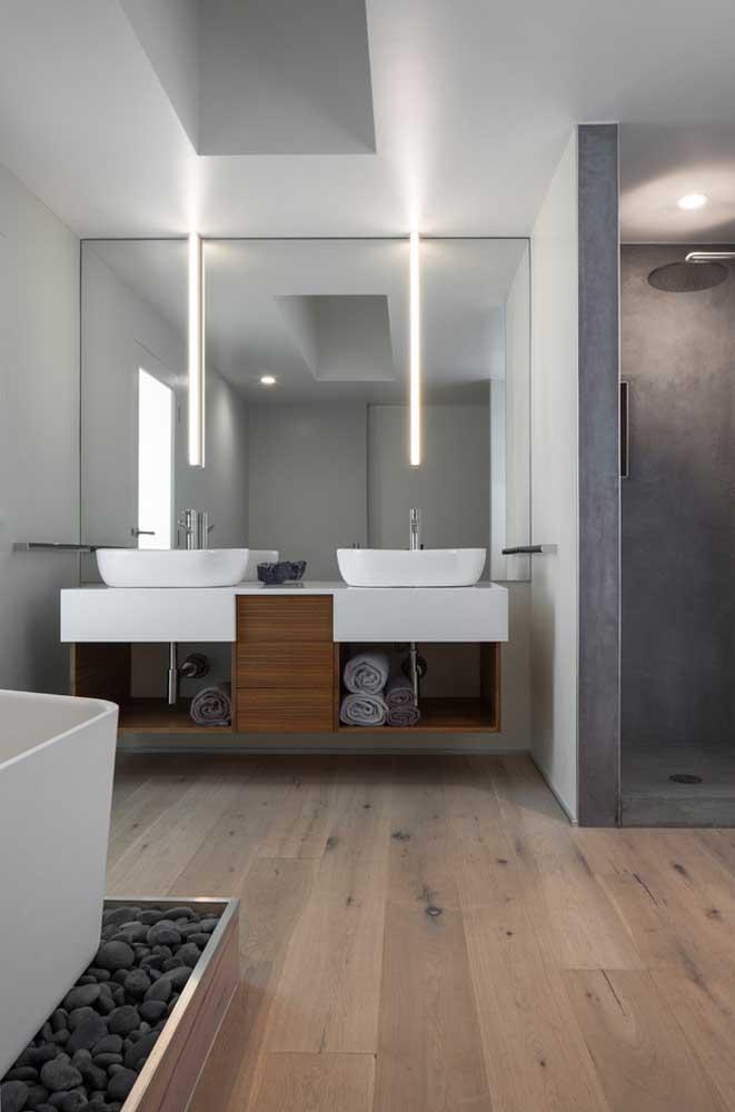 Gabinetes planejados foram escolhidos para o projeto deste banheiro; perceba que a iluminação foi propagada graças ao espelho eleito para compor o ambiente