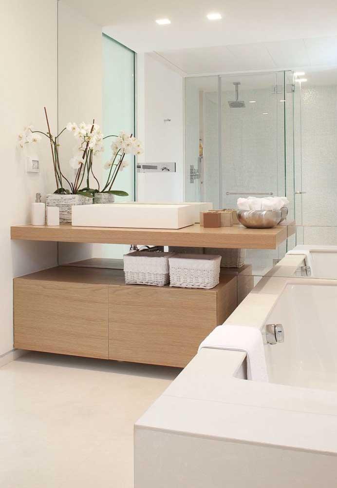 Esse banheiro planejado acertou em cheio na hora de aproveitar o espaço trazendo box de vidro, espelhos grandes e revestimentos em tons claros
