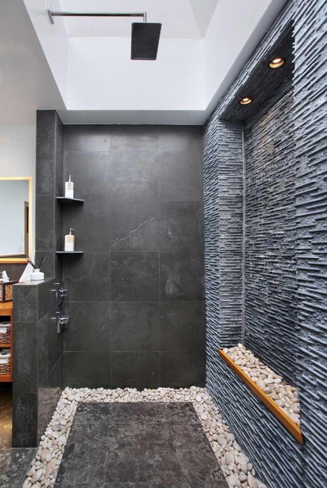 Nichos e prateleiras dentro do box ajudam na organização e aproveitamento do espaço; destaque para as bordas laterais com pedras e a parede revestida com textura semelhante a pedras