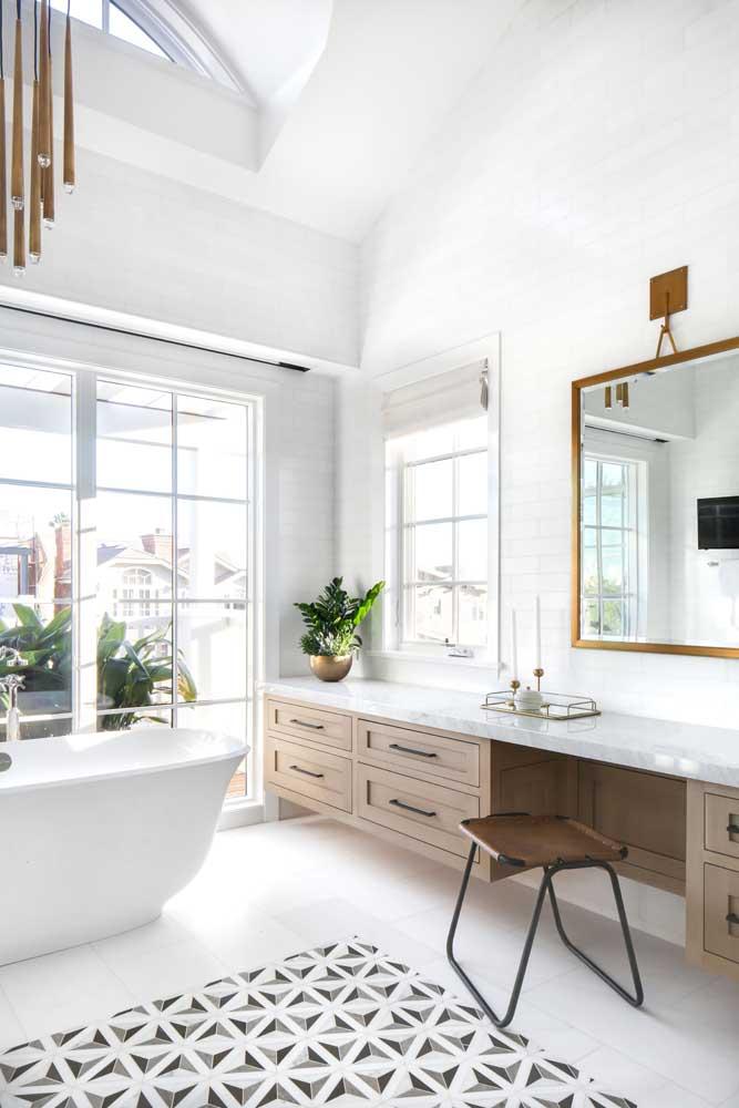 Banheiro planejado grande e com banheira; os armários e gavetas sob medida junto ao balcão de mármore completam a proposta