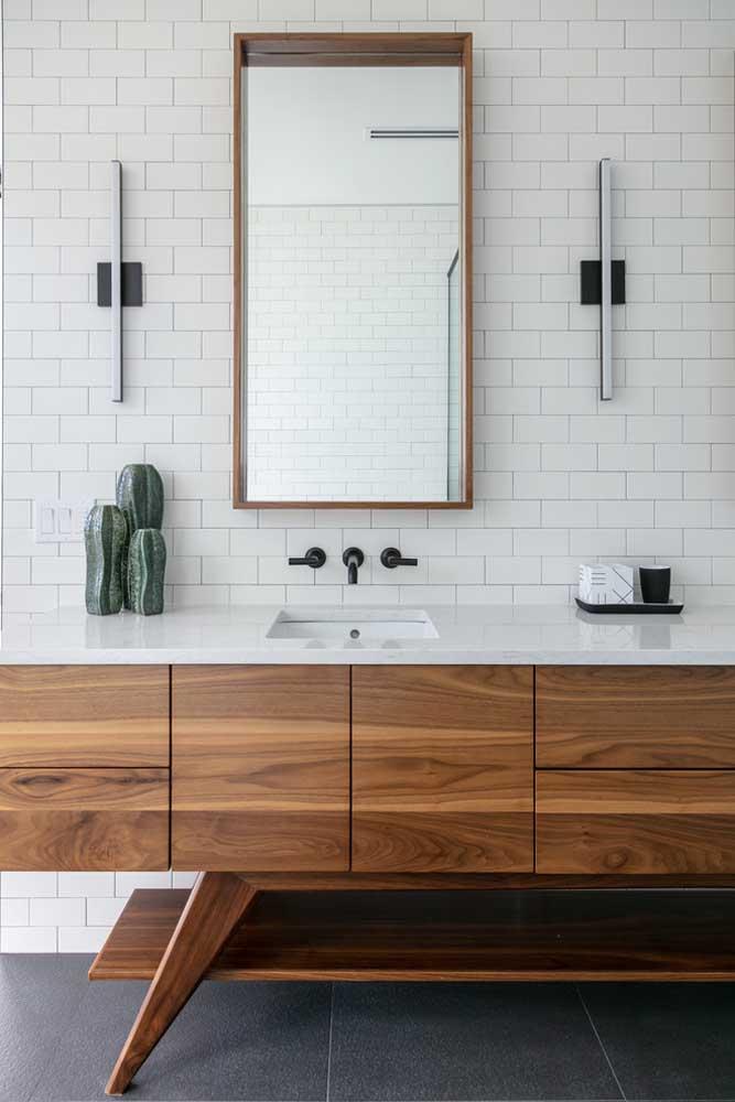 Armário planejado para banheiro em madeira; a parede de cerâmica branca completa o visual com chave de ouro