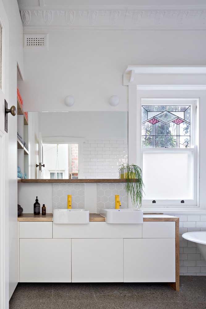 Banheiro planejado, com boa entrada de luz natural, gabinete sob medida e espelho grande