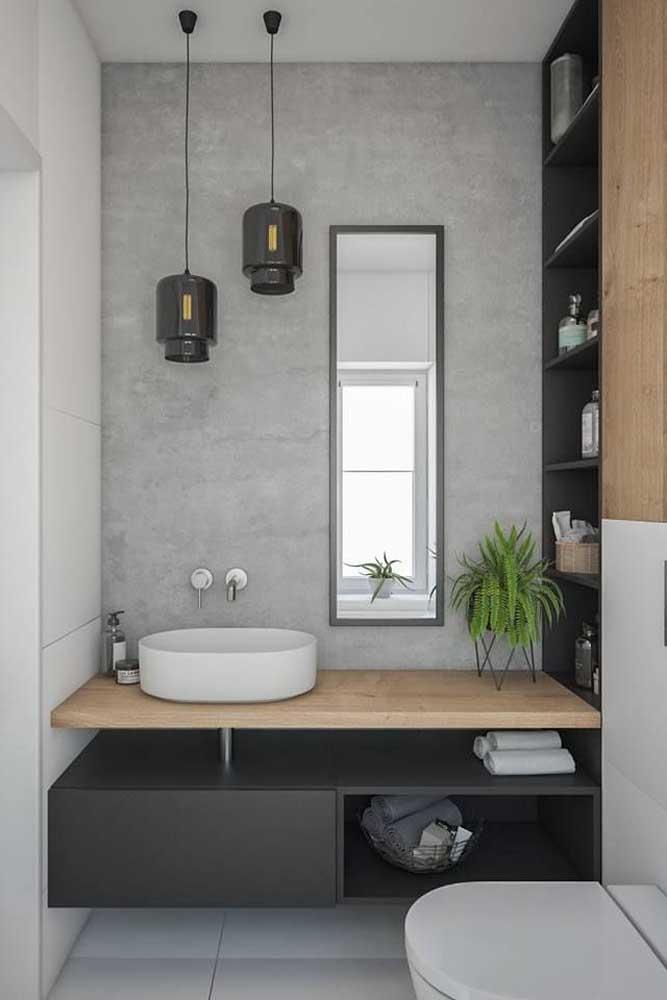 Banheiro planejado pequeno, com gabinete sob medida e armário embutido com prateleiras; o toque final fica por conta da parede de cimento queimado