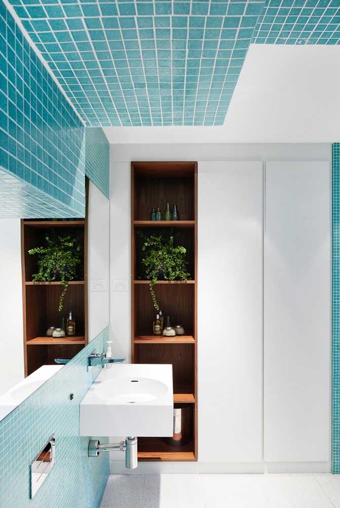 Este banheiro planejado e colorido em azul e branco contou com armários e prateleiras sob medida