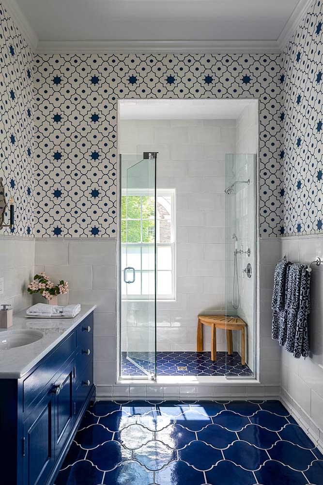 O banheiro planejado em tom de azul royal de azul ganhou uma porta de vidro para o box, além de um armário sob medida na mesma cor dos revestimentos