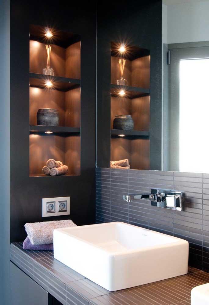 Os nichos embutidos com spots trazem elegância e organização para esse banheiro planejado