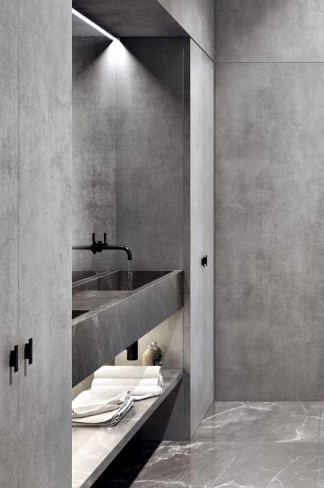 Banheiro em cimento queimado, com prateleiras de alvenaria para aumentar a organização do ambiente