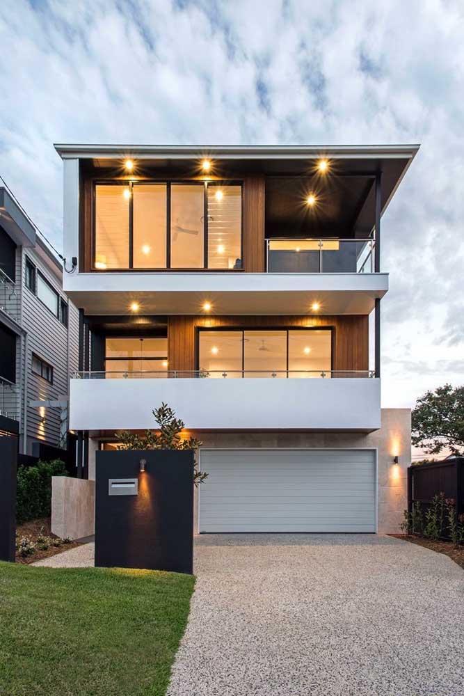 Fachada de casa grande e moderna com telhado embutido; destaque para as janelas amplas que permitem a entrada da luz natural em abundância