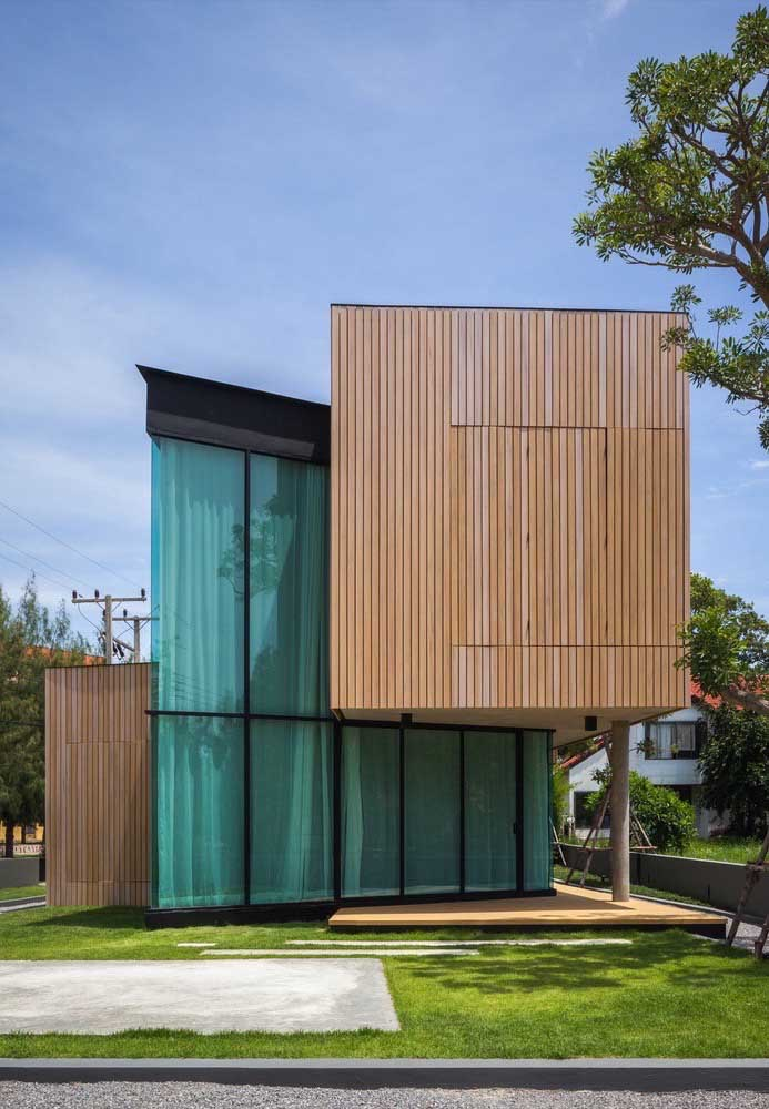 Incrível o mix de madeira com vidro nessa casa grande de arquitetura moderna