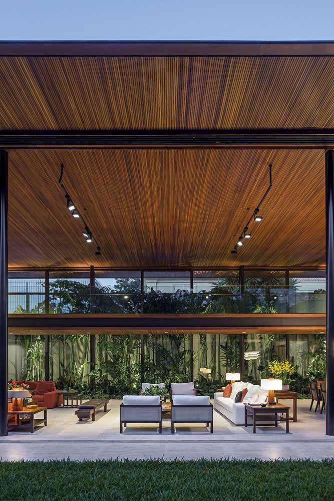 Uma casa grande com pé direito duplo para ninguém botar defeito; repare que o teto de madeira deixa a sala de estar ainda mais exuberante