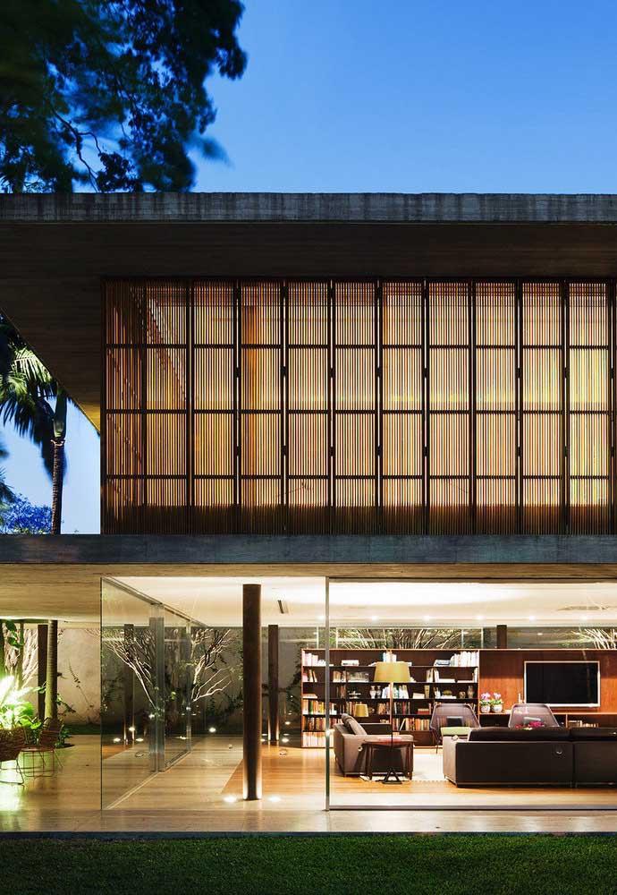 As paredes de vidro do piso superior é o grande destaque dessa casa grande