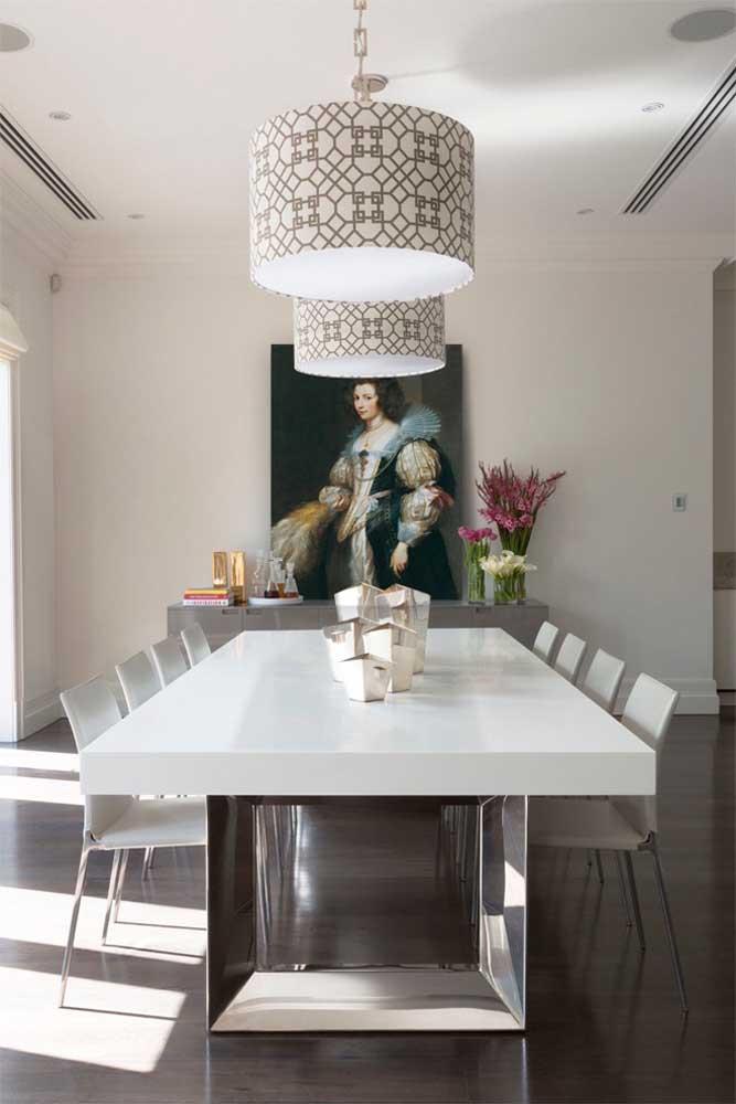 Sala de jantar de casa grande: janelas amplas, mesa grande, quadro gigante na parede e luminárias suspensas; repare que o segredo da decoração de ambientes amplos é a proporção