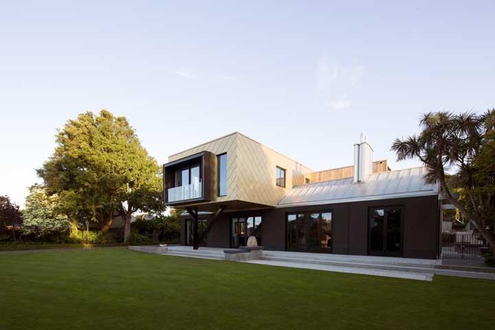 Casa grande moderna em tons terrosos para combinar com o amplo espaço verde na área externa