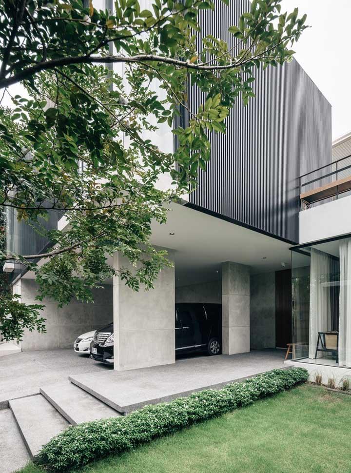 Casa grande com garagem coberta; a entrada se destaca pelos degraus grandes e ornamentados pela grama