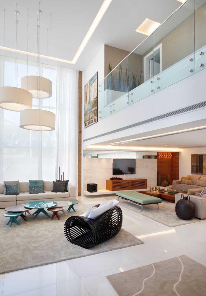Visão do interior de uma sala de casa grande; ambientes bem marcados e decoração impecável