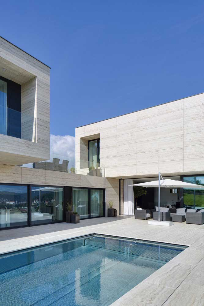 Casa grande moderna com piscina; o que chama atenção nesse projeto é o formato em L da construção