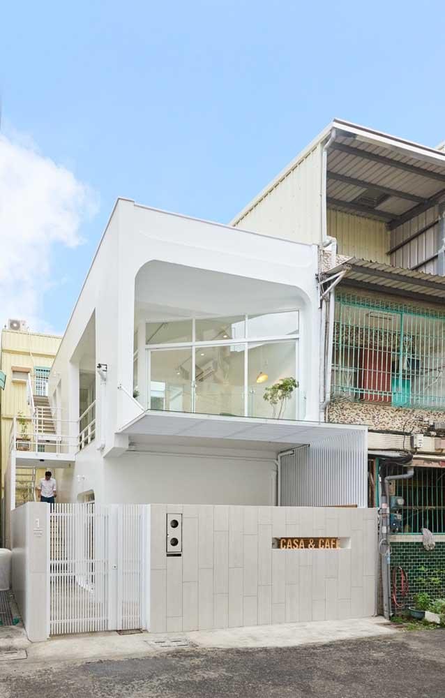 As grandes janelas de vidro garantem luz natural e leveza na fachada da casa pequena