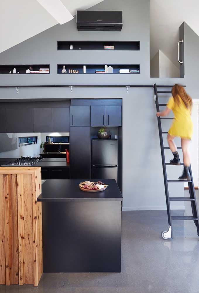 Nessa casa pequena, a escada com trilho facilita o acesso ao mezanino e as prateleiras altas