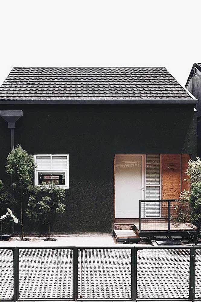 Fachada de casa pequena e simples; a pintura preta é o diferencial desse projeto
