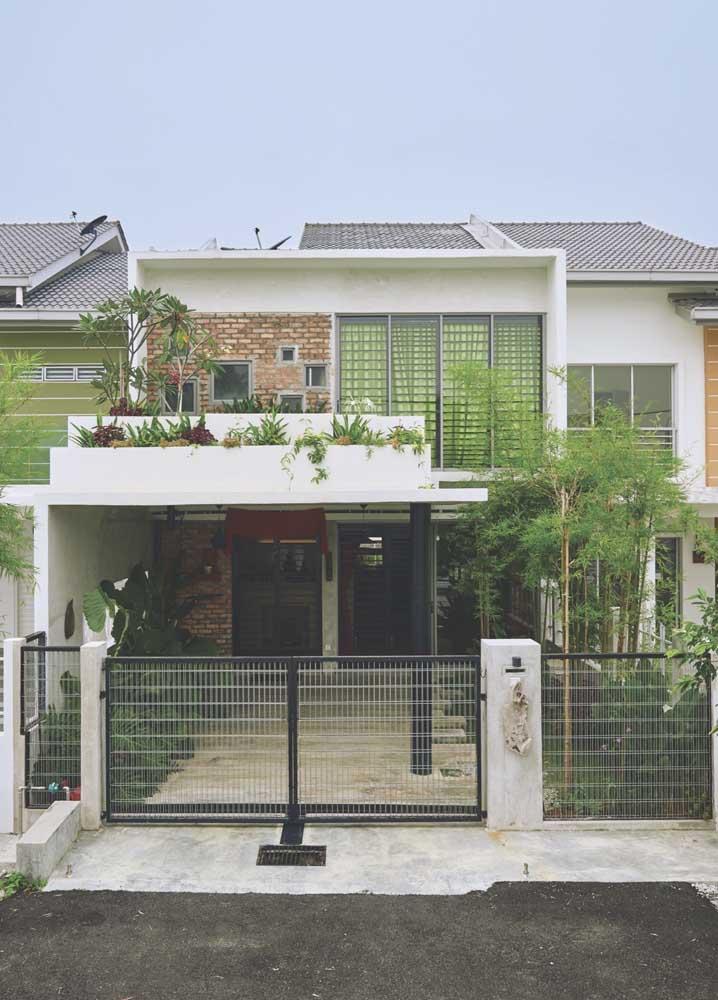 Uma casa simples destacada pelo jardim na entrada e pelo uso de tijolinhos aparentes na fachada