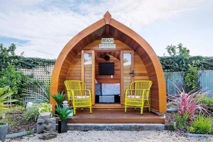 Mini casa de madeira no jardim; todo o destaque aqui vai para o formato diferenciado do projeto