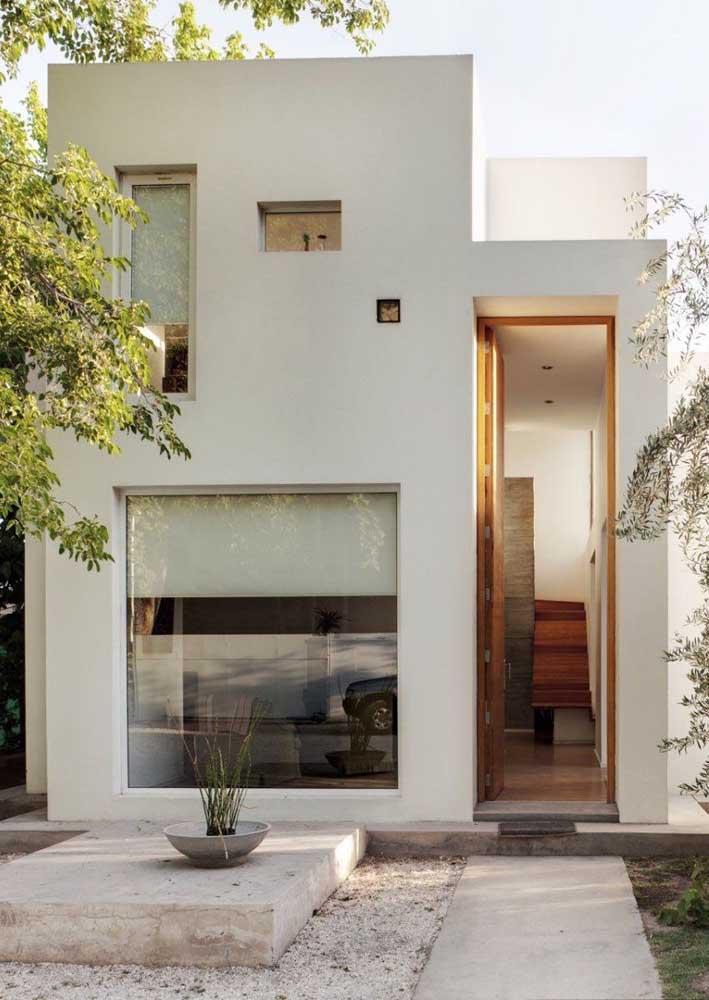 Fachada de casa simples moderna; destaque para as janelas de vidro que garantem uma entrada maior de luz natural