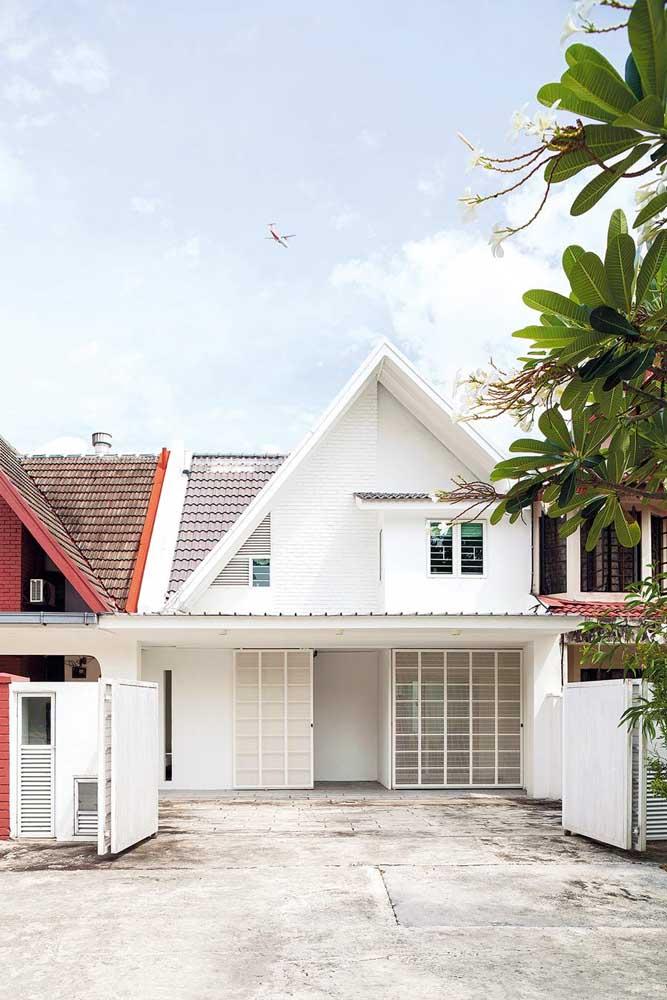A casa térrea branca e simples da imagem conta com uma pequena garagem na frente